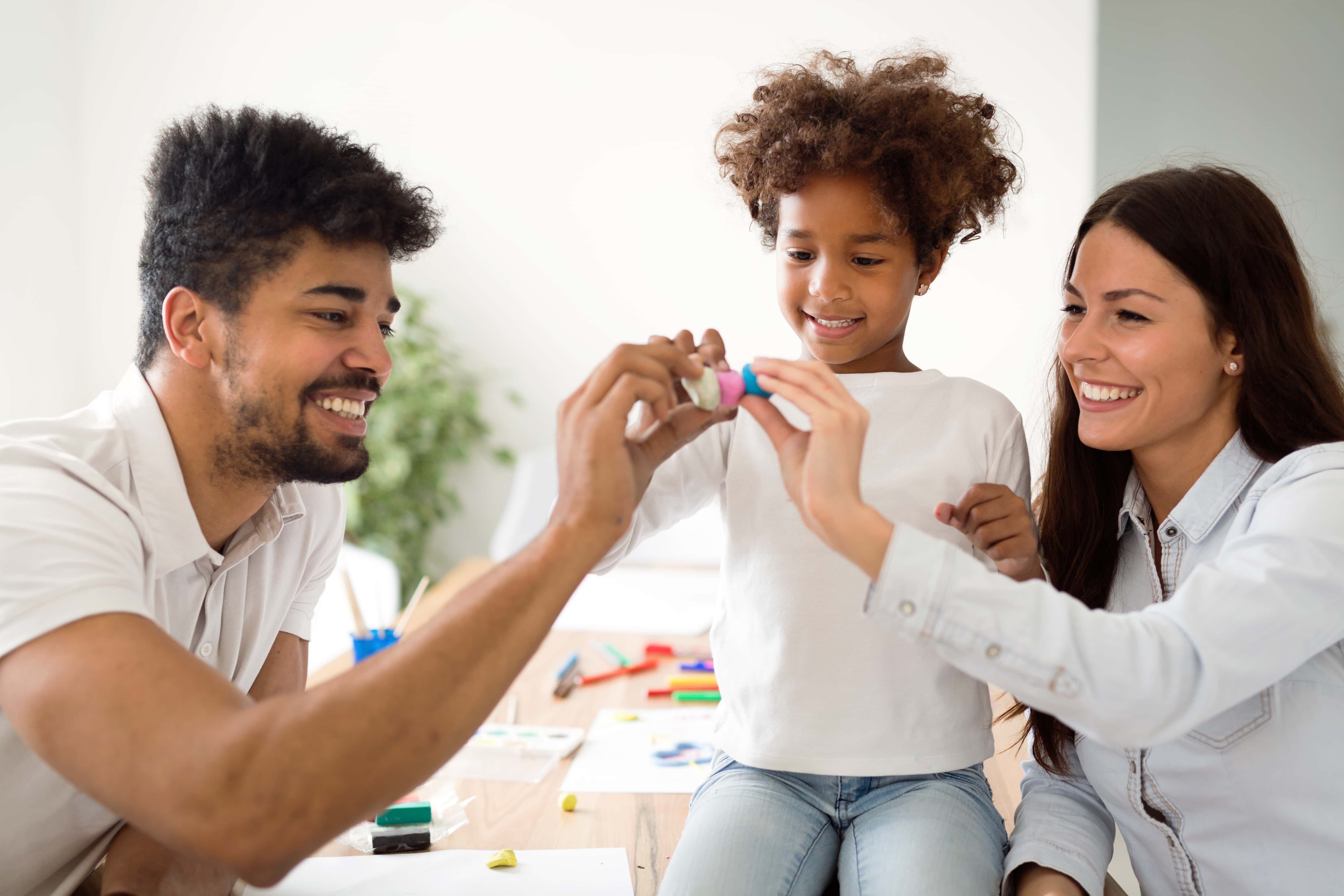 Foster parents play with their adopted girl