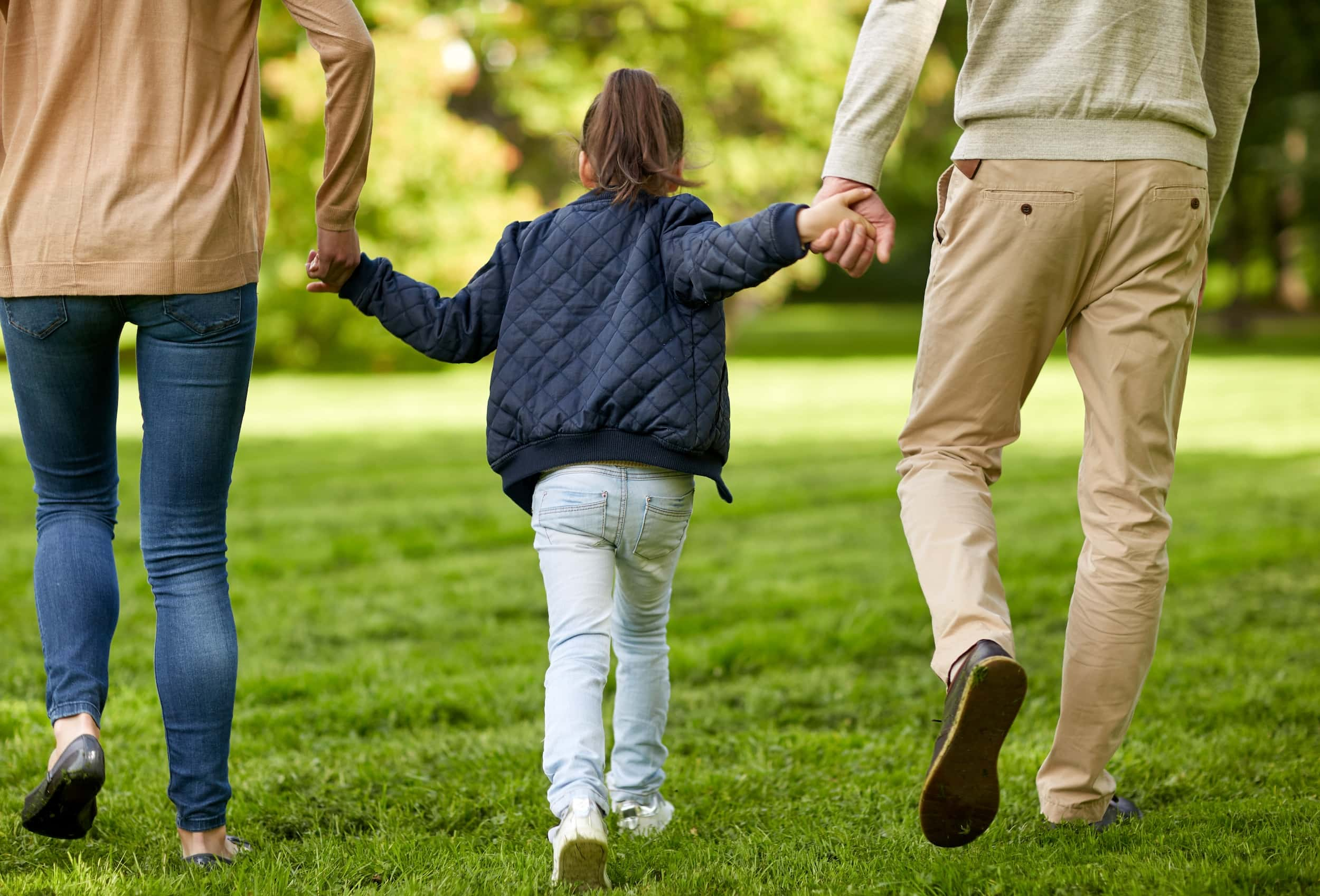 New foster parents walk with their recently adopted child